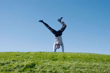 somersault: Happy businessman doing somersault on grass