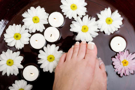 Womans feet in bowl of water photo