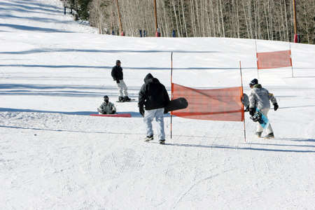 Snowboarders carrying their snow boards