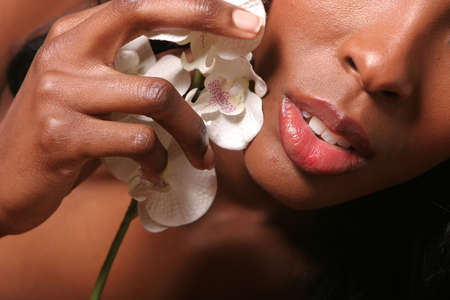 african american spa: Lips of a beautiful sexy African American woman with orchid Stock Photo