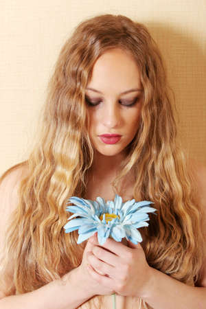 Pretty sexy woman holding a blue daisy photo