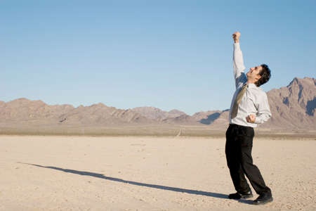 Happy businessman in the desert