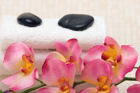 Spa towels, massage stones and pink orchid Stock Photo