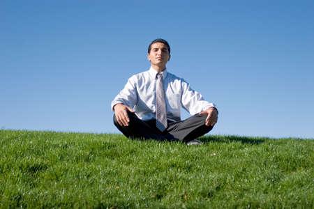 Businessman meditating on green grass Stock Photo - 2291893
