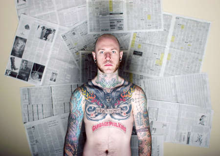 Tattoo man in front of newspapers photo
