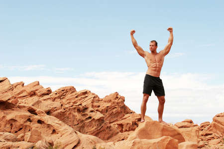 sixpacks: Muscular man on red rocks Stock Photo