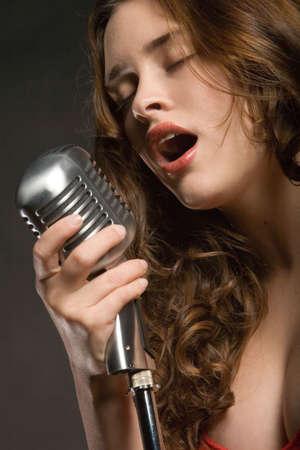 Beautiful sexy young woman singing photo