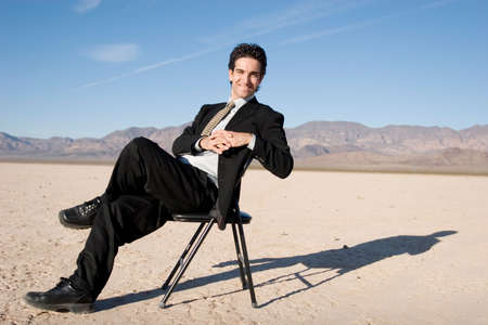 Smiling businessman sitting on a chair photo