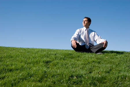 man meditating: Businessman meditating on green grass Stock Photo