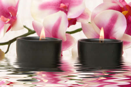 retreats: Aromatherapy candles and pink orchid Stock Photo