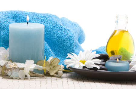 Massage stones, candle and daisies