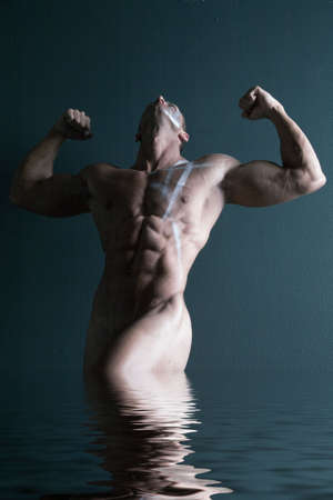 nude man: Sexy body builder flexing his muscles Stock Photo