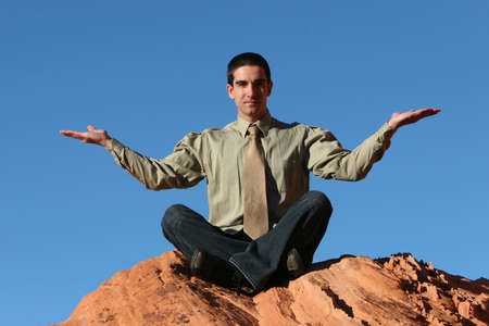 Businessman meditating on red rocks photo