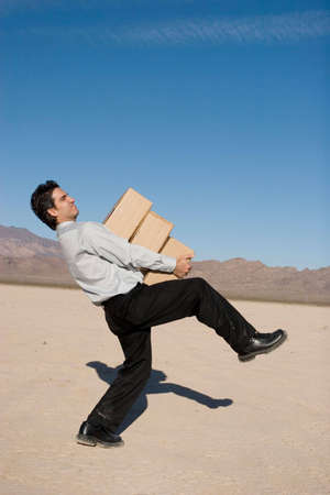 Businessman carrying heavy boxes photo
