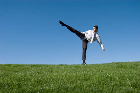 Businessman doing karate moves on green grass photo