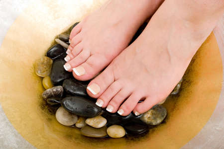 Womans feet in bowl of water and rocks Imagens