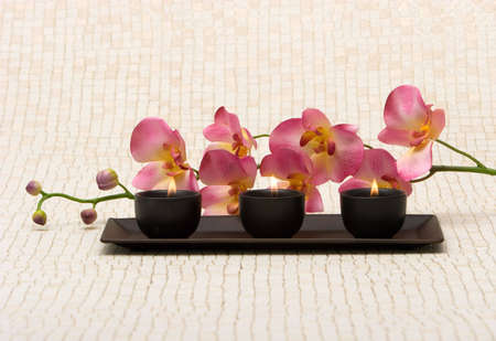 Aromatherapy candles and pink orchid Stock Photo