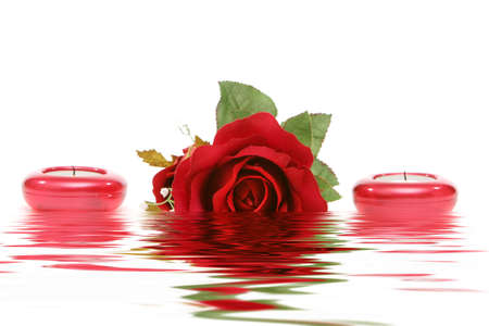 Beautiful red rose and candles isolated on white background photo