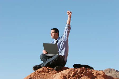 ecstatic: Ecstatic businessman working on laptop