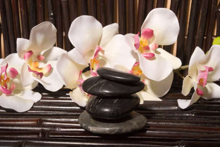 Massage stones and orchid flowers on bamboo Stock Photo - 2733509