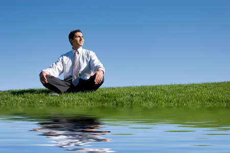 Businessman meditating on green grass Stock Photo - 2950547