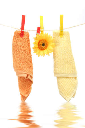 orange washcloth: Towels hanging on the rope by clothespin