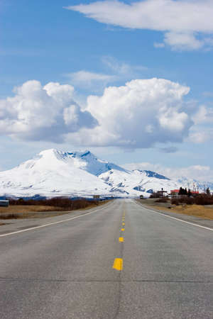 Highway running by the snowy Alaska mountains photo