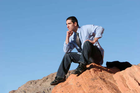 Young businessman sitting on red rocks
