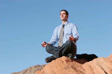 calmness: Businessman meditating on red rocks