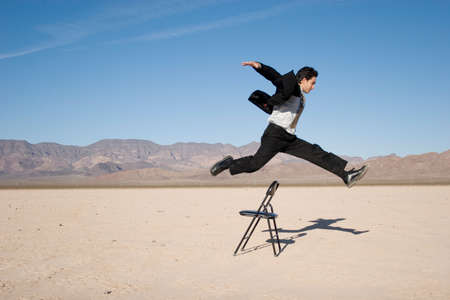 Businessman jumping over a chair