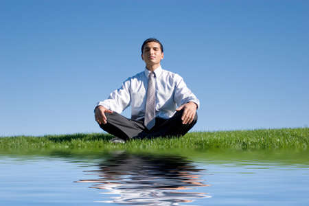 Businessman meditating on green grass Stock Photo - 2987612
