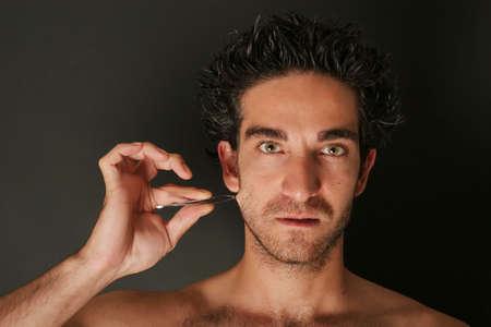 Man pulling his beard with tweezers Banco de Imagens