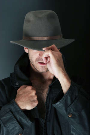 courteous: Attractive man with hat and trenchcoat Stock Photo