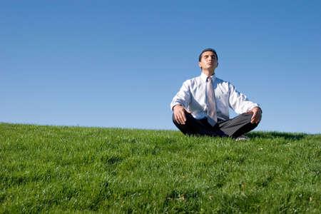 Businessman meditating on green grass photo
