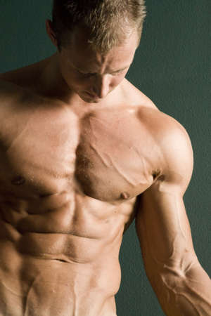 Muscular body builder showing muscles photo
