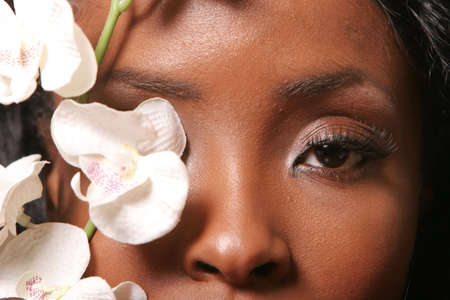 Beautiful black woman with orchid on her face Stock Photo