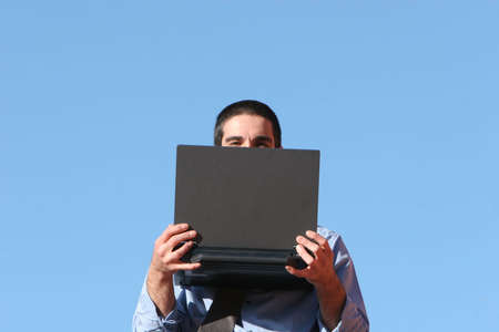Businessman with his laptop against blue sky