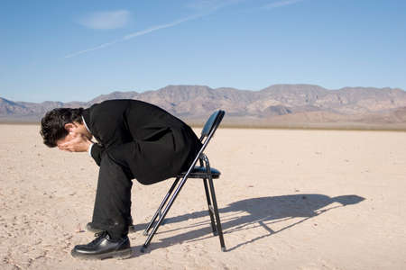Businessman sitting alone in the empty desert photo