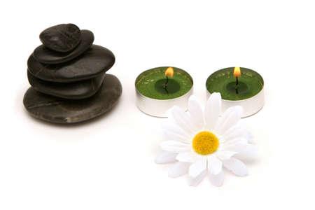石、蝋燭および白い背景のヒナギク 写真素材