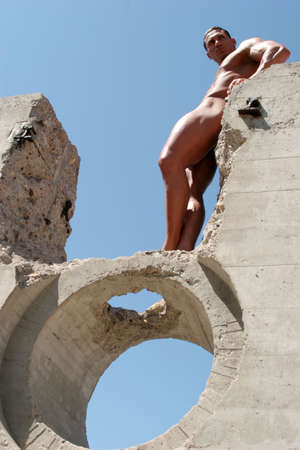 Muscular man posing in concrete ruins photo
