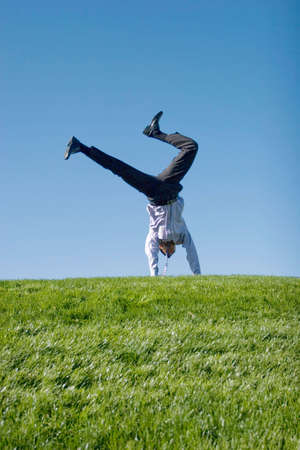 Happy businessman doing summersault on grass Stock Photo - 3378013