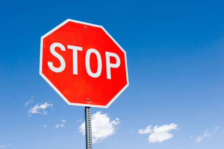 road warning sign: Stop sign for traffic against blue sky