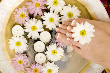 Daisies, candles and pedicured feet photo