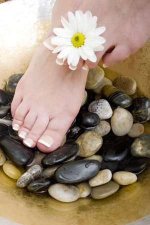 Womans feet in bowl of water and rocks photo