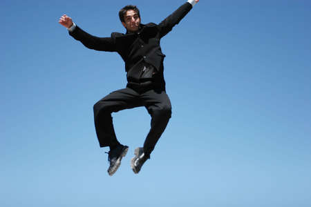 Ecstatic businessman jumping in the air photo