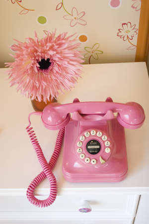 nightstand: Pink telephone and daisy on nightstand