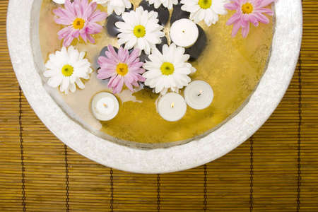 rejuvenating: White daisies and spa candles in water