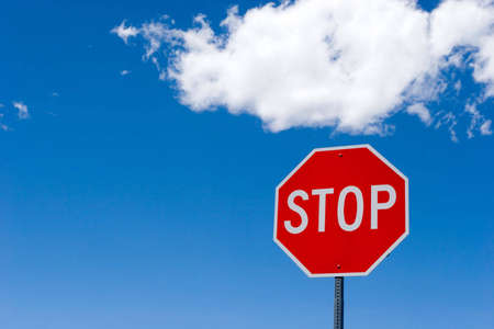 Stop sign for traffic against blue sky photo