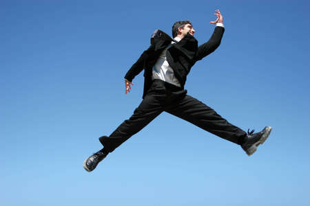 Successful businessman jumping to celebrate photo