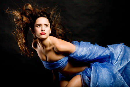 Beautiful young woman with long hair dancing photo